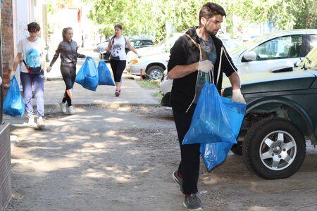 plogging. le ragazze corrono e raccolgono la spazzatura nei sacchetti per le strade