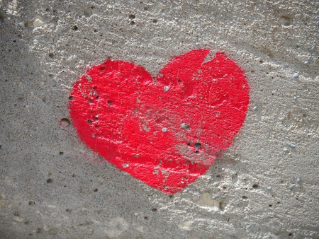 heart painted on a concrete wall, a symbol of love.