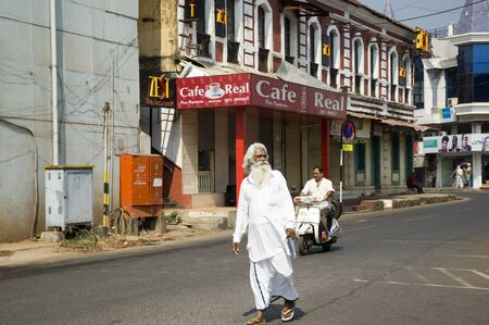 an old man with a gray beard in white clothes walking the streets of the city