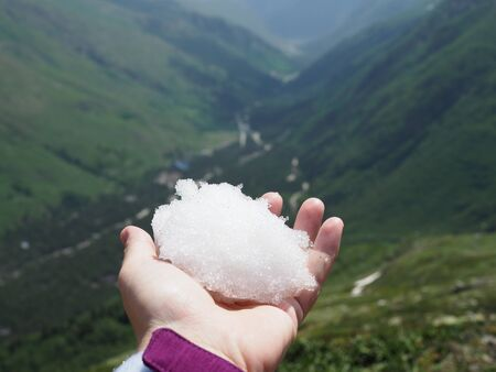 white snowball in hand on a background of picturesque mountains on a Sunny summer day.