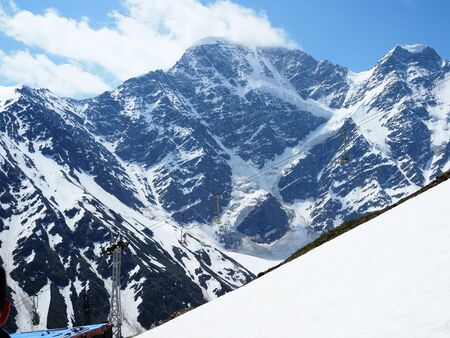 High snowy Caucasian mountains with a glacier with the form of a figure of seven number. Peaks of the mountains Donguz Orun and Nakra Tau. Elbrus region, Cheget. Banco de Imagens