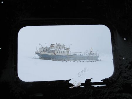 Abandoned warship at the coast of Arctic ocean in winter snowstorm