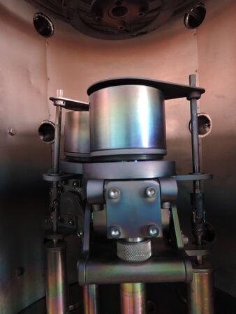 Rainbow on coated steel rods inside vacuum deposition chamber.