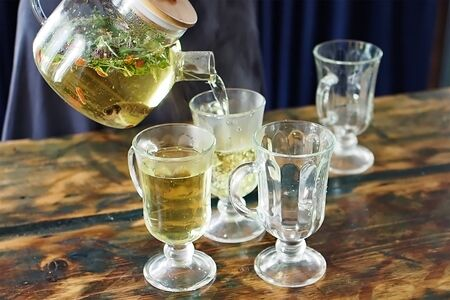 process of pouring herbal tea in a transparent teapot into beautiful glass glasses.