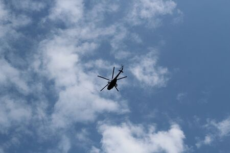 large military helicopter hovers in sky. A camouflaged helicopter flies at high speed 免版税图像 - 128401757