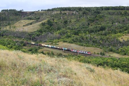 A long train loaded with double-stack cargo containers winds its way around tight s-curves in mountain countryside. All ID marks removed
