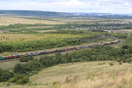 A long train loaded with double-stack cargo containers winds its way around tight s-curves in mountain countryside