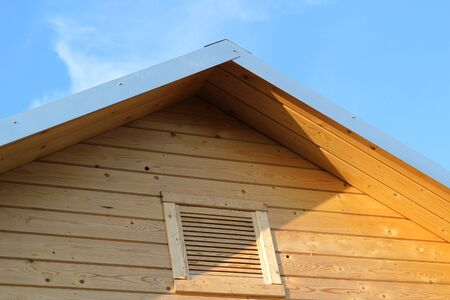 Fragment of just installed wooden roof eaves with ventilation grille. House improvement concept