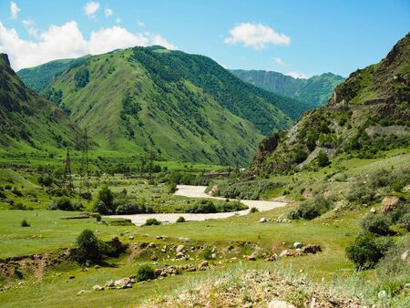 beautiful mountain landscape with a river flowing across the plain on a Sunny summer day.
