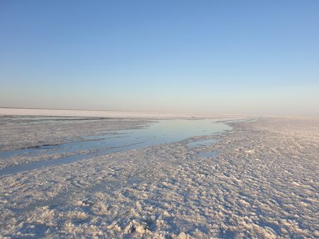 white surface of the lake covered with salt at sunrise.