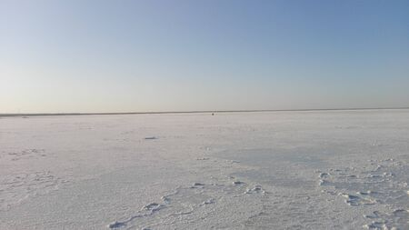 white surface of the lake covered with salt at sunrise