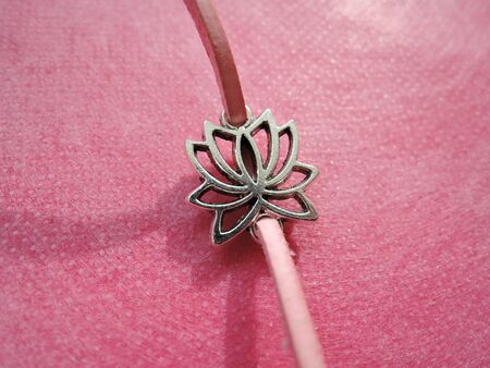 Natural fashionable bracelet with a pendant in the form of a Lotus flower on a pink background