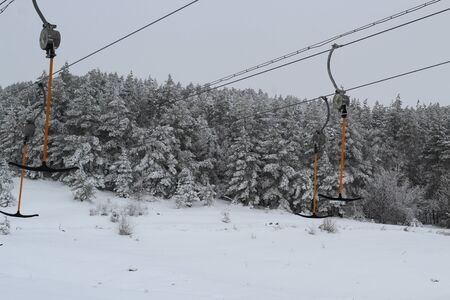 Ski-lift for skiers and snowboarders with sticks in winter on a snowy hill.