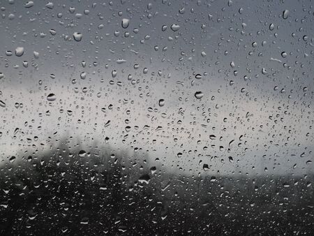 beautiful raindrops on the glass through which you can see the stormy gray sky.