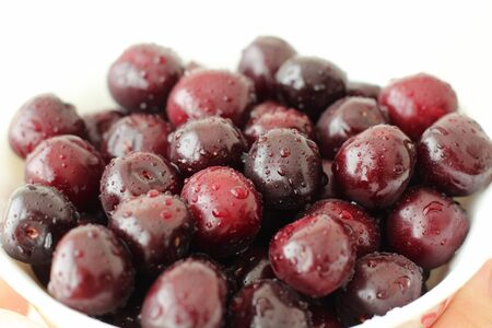 Full plate of fresh cherries berries covered with drops of water Stockfoto
