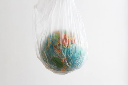 ball in the form of a globe is in a plastic bag. concept of plastic pollution of the earth Stockfoto