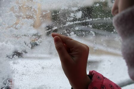 kid drawing on fogged glass in winter Stockfoto