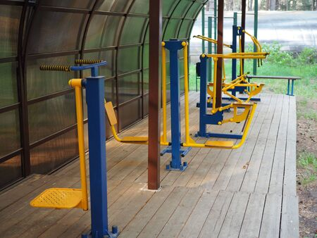 Colorful outdoor fitness equipment in summer under the shed.