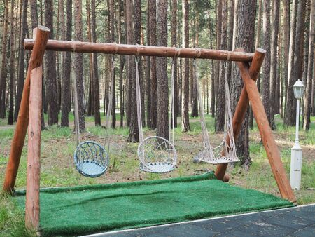 Hanging rope chair or swing in the forest in a wooden patio.