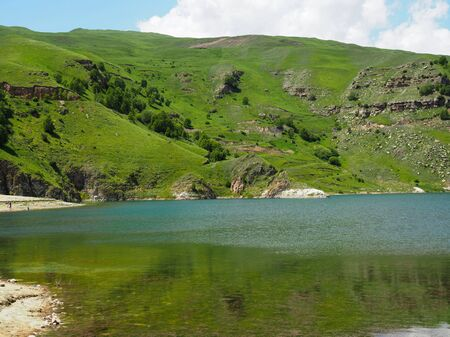 Panorama of a mountain lake with beautiful blue or turquoise colored water.