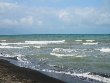 beautiful waves in the sea and black sand.