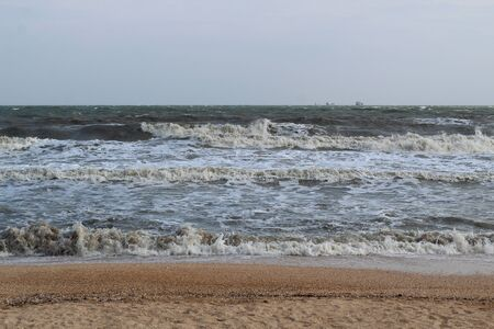waves during a storm at sea. in the distance you can see large ships and barges.