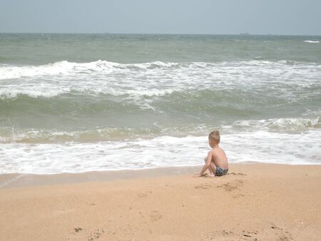 Back view ,Young kid sitting on the beach and looking forward at the waves on blue sky background