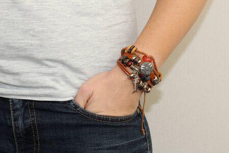 Ethnisches Herrenarmband am Arm Die Hand des Mannes trägt ein Armband in der Jeans.