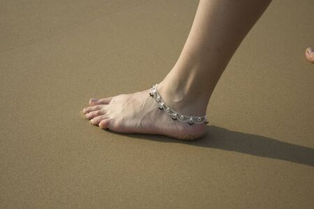 Closeup of a woman's legs with an anklet jewelry on the beach. Banque d'images