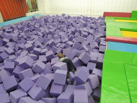 Child boy in foam rubber pit throwing colored cubes