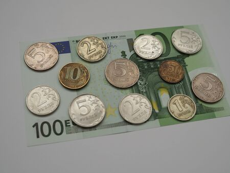 ruble coins are placed on top of the 100 Euro banknote