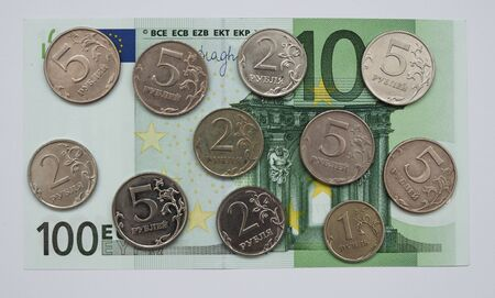 ruble coins are placed on top of the 100 Euro banknote financial crisis 2020. Фото со стока