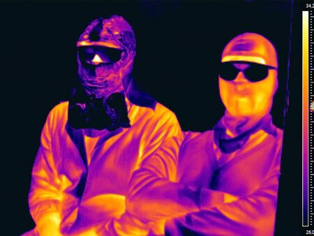 image in the thermal imager of two people in masks and glasses
