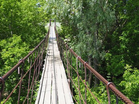 suspended wooden bridge over the river in the forest.