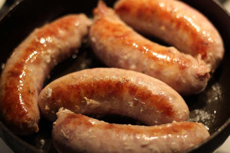 Soft focus photo. Fried sausages on the pan. Unhealthy breakfast. English and German style cuisine. 版權商用圖片
