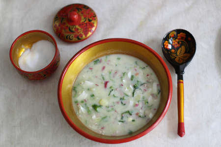 Okroshka. Traditional Russian summer cold soup with sausage, vegetables and kvass in bowl on wooden background. Top view