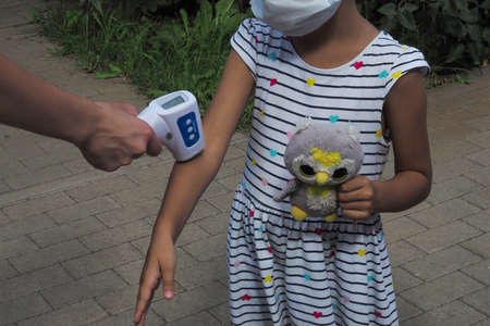 Russia, Vorinezh region - august, 2020: children with face mask at school after covid-19 quarantine and lockdown. temperature check in school kid girl at school.