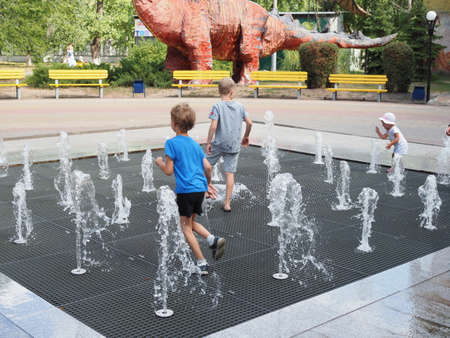 Russia, Boronezh region - august,2020: Toddler playing with small fountains on the urban plaza. 新聞圖片
