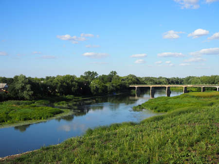 Beautiful summer landscape with a view of an old vintage bridge over a small river