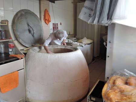 Russia, Sochi - june,2016 : Baker making turkish pita bread in tandoor clay oven . Baking process. Many fresh hot bread in the basket