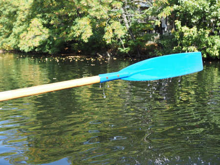 Blue plastic paddle paddles over the water after a close-up stroke. Water drops flow down