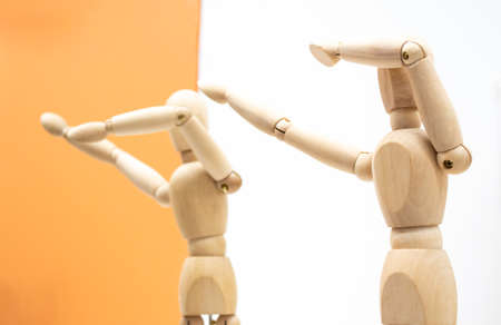 Two wooden human figures on white and orange backgrounds dance and make a dab movement sneezing gesture.