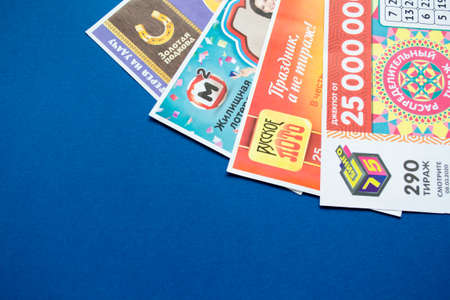 Moscow, Russia, July 2020: Close up of various Russian lottery tickets on a blue background. Russian Lotto. Редакционное