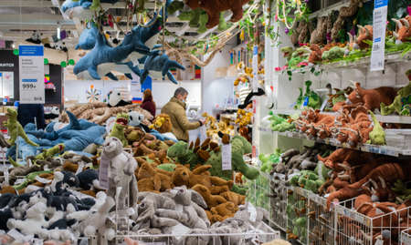 Moscow, Russia, February 2021: A bunch of soft toys on the shelves in an Ikea store: sharks, dinosaurs, bunnies, dogs. Toys on shelves, on the ceiling and in baskets. Buyers on background. Redactioneel