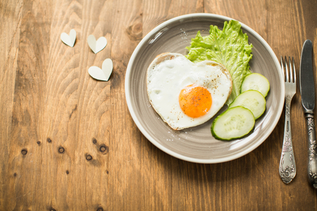 desayuno romantico: Romantic breakfast with scrambled eggs in a heart-shaped Valentines Day