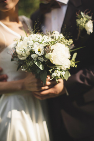 a newly married couple: Bride and groom holding bridal bouquet Stock Photo