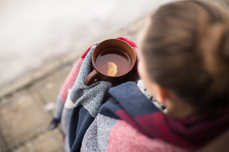 checkered scarf: Girl in rug drinks hot tea in winter Stock Photo