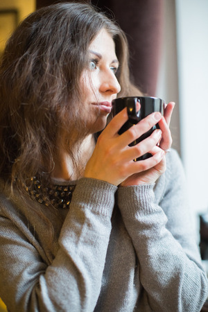 snug: girl drinks hot tea at the window Stock Photo