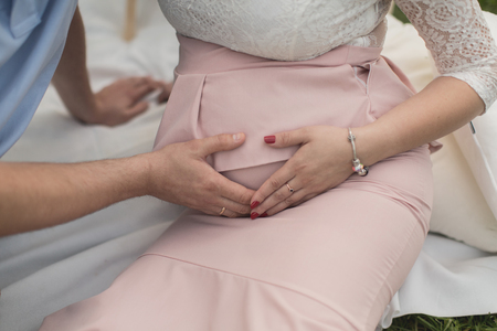 beautiful womb: Belly of pregnant woman with her husband hands Stock Photo