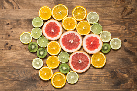 Fresh citrus fruits half cut on wooden background